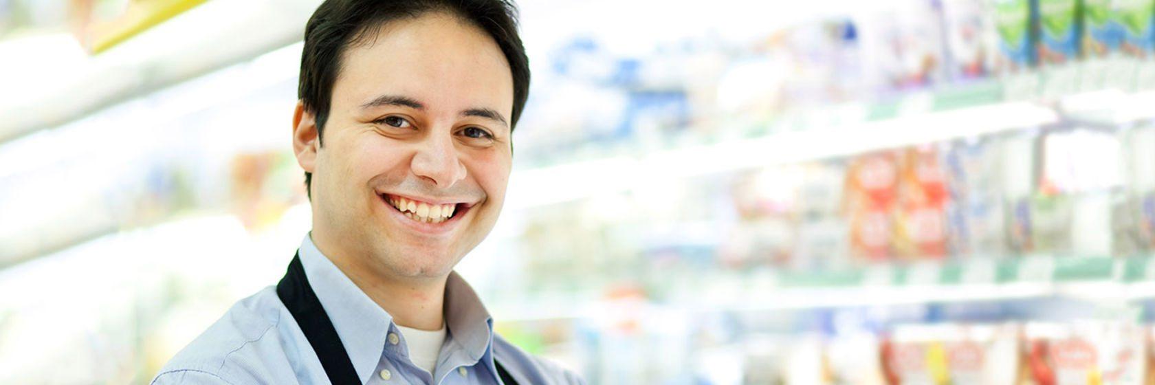 Mann mit dunklen Haaren freut sich, mit Hilfe des waff einen Job im Einzelhandel gefunden zu haben.