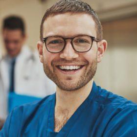 Mann mit Hornbrille freut sich mit Hilfe des waff einen Job als Pflegeassistenz gefunden zu haben.