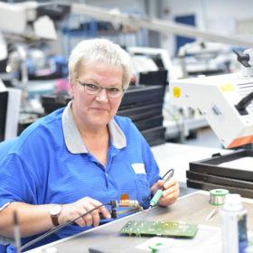 Portrait ältere Frau in einer Fabrik zur Montage von moderner Elektronik am Arbeitsplatz