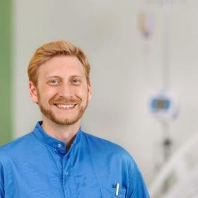 Bild zeigt einen Krankenpfleger vor einem leeren Spitalsbett