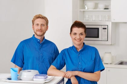 Bild zeigt einen Krankenpfleger und eine Krankenpflegerin in einer weißen Spitalsküche