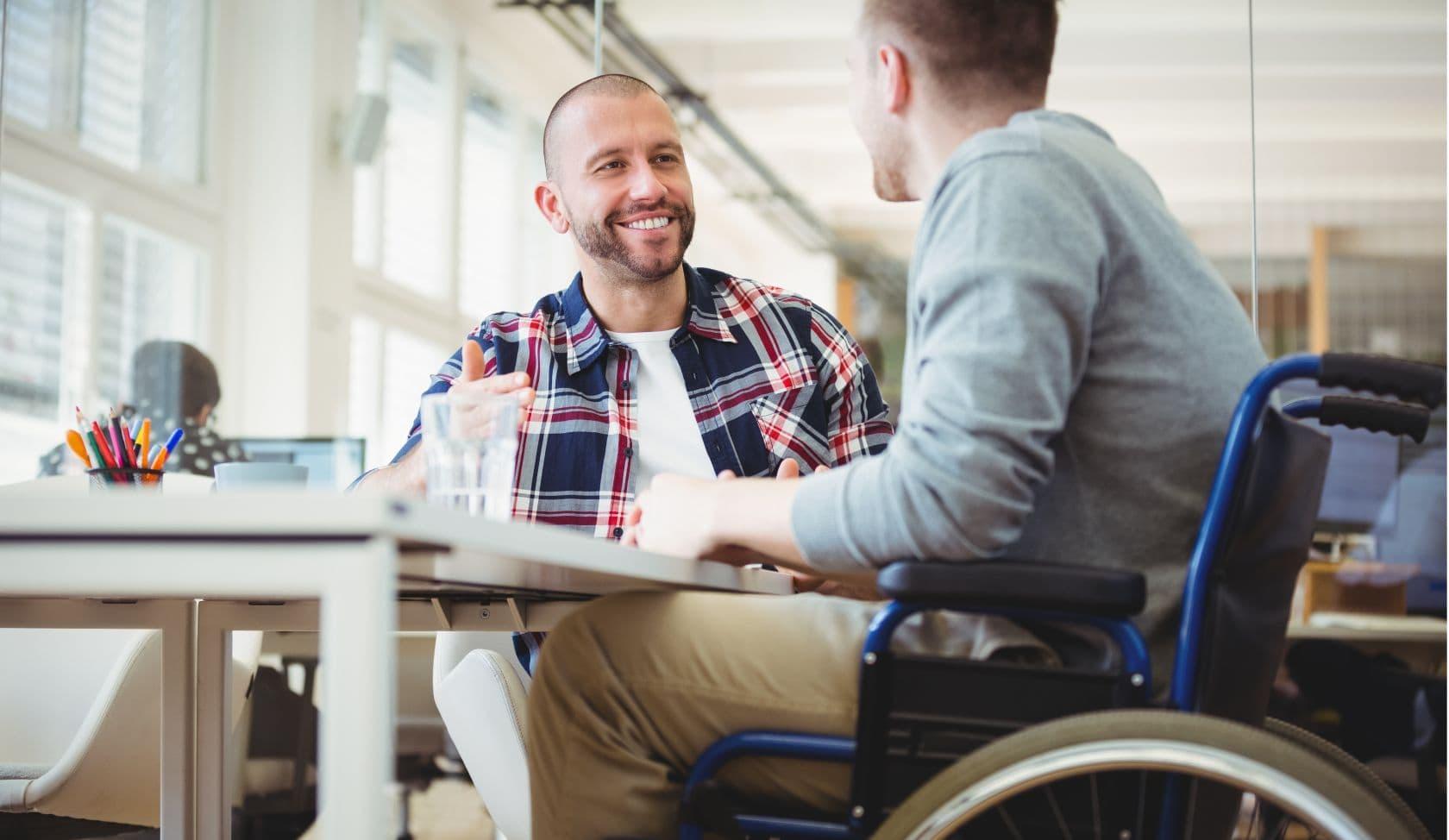 Beratungsgespräch zwei sitzende Männer einer davon im Rollstuhl