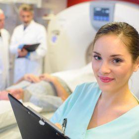 Radiologie Technikerin steht vor einem Patienten, der eine radiologische Untersuchung hat, und schaut in die Kamera.