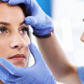Orthoptikerin untersucht die Augen einer jungen Frau.