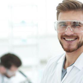 Biomedizinischer Analytiker in seinem Arbeitsumfeld lächelt ins Bild.