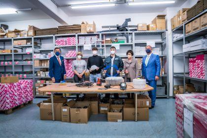 Stadtrat Peter Hanke, Wirtschaftskammerpräsident Walter Ruck und AMS Wien Chefin Petra Draxl stehen mit Lehrlingen in einem Raum an eine Tisch mit Elektrogeräten